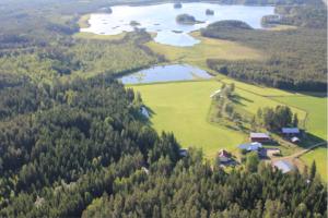 Kuvassa on järvi- ja metsämaisemaa, jossa on maatilakeskus keskellä.