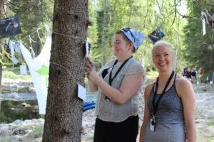 Vesistökoulun työpajatuloksia kiinnitettään puuhun.