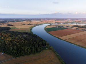 Kuvassa peltomaisemaa halkaisee joki.