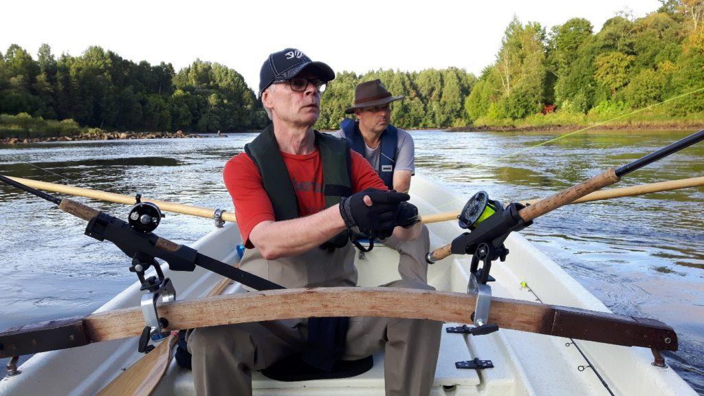 kaksi mieskalastajaa soutuveneessä.