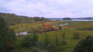 Kaivinkone kaivaa Tyköjärvellä uutta uomaa.
