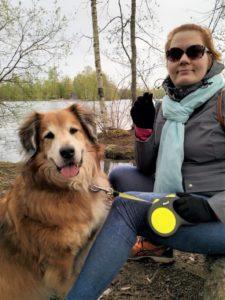 Virve Rinnola (kirjoittaja) istuu kuvassa vesistön äärellä koiransa kanssa.