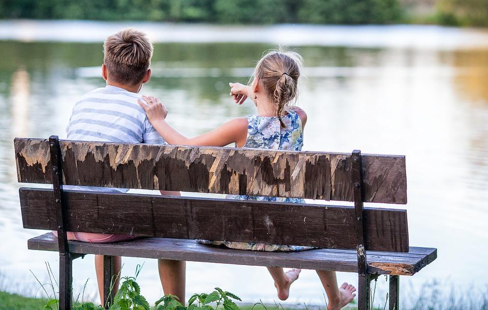 Kaksi lasta istuu penkillä ja katsovat vesistöä. Toinen lapsista osoittaa jotakin kaukaa maisemassa.