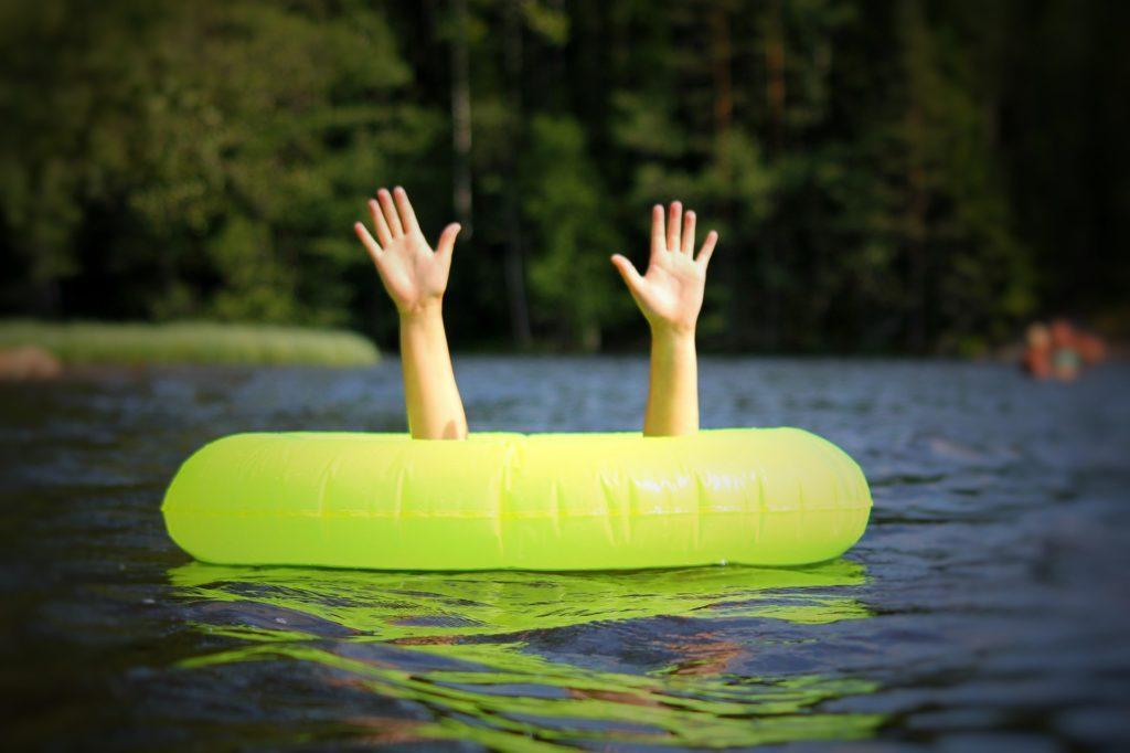 Tyttö nostaa kädet ulos pelasturengaasta järvessä ollssaan. Kuva kertoo hädästä.
